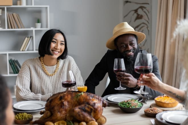 positive multiethnic couple drinking wine with guest - Best Thanksgiving Jokes