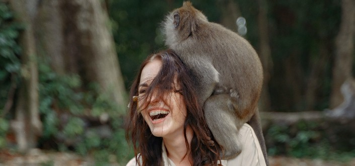 a woman laughing while a monkey is on her shoulder