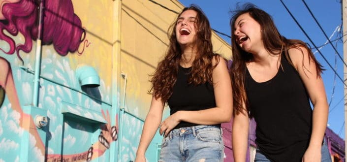 two women laughing under the bright sun