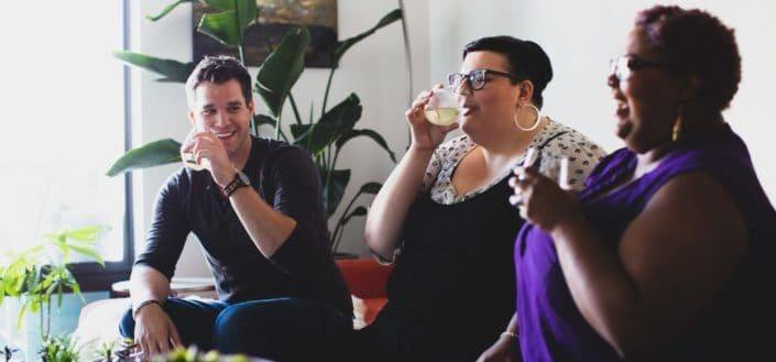 three people enjoying their drinks