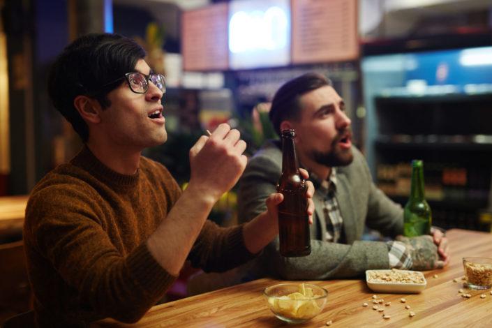 Two guys, drinking beer, reacting on something interesting.