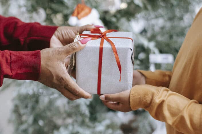 man handing a gift over to a woman
