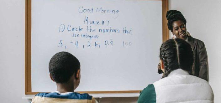 woman teaching math to two kids
