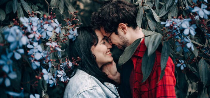 couple having a sweet photoshoot with flowers on the background
