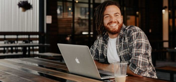 man with a laptop smiling