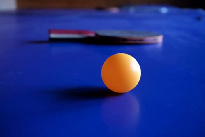 a pingpong ball with a paddle behind it
