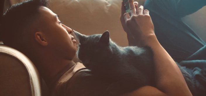 Guy on a couch with his cat, browsing his phone.
