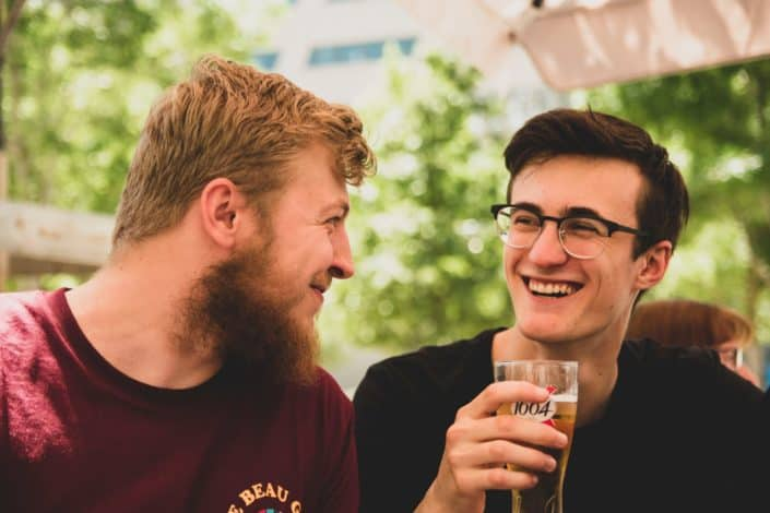 two men smiling at each other, the other holding a glass of beer