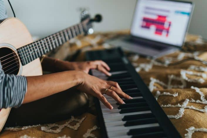 woman with a guitar has her hands on a piano