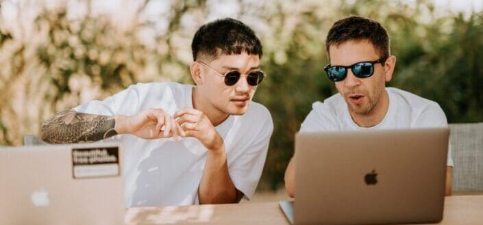 two men wearing shades looking at the laptop