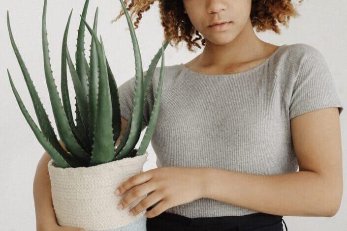 woman holding an Aloe Vera plant