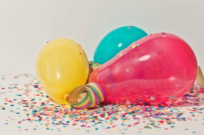 three balloons with confetti around them