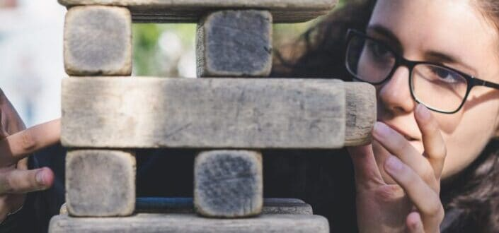 woman with eyeglasses trying to remove a jenga block from a jenga tower