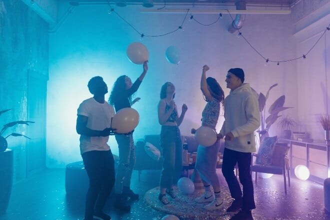 group of friends dancing while holding balloons - birthday party games