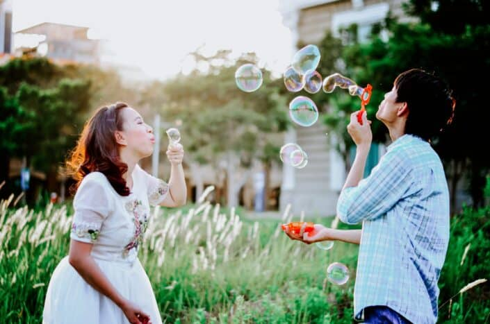 mana nd woman blowing bubbles outdoors