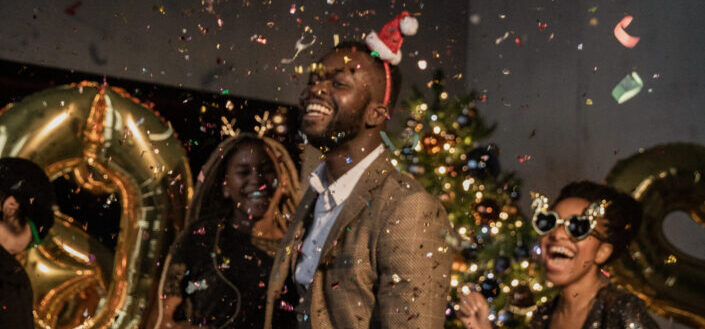 three people at a party surrounded by confetti