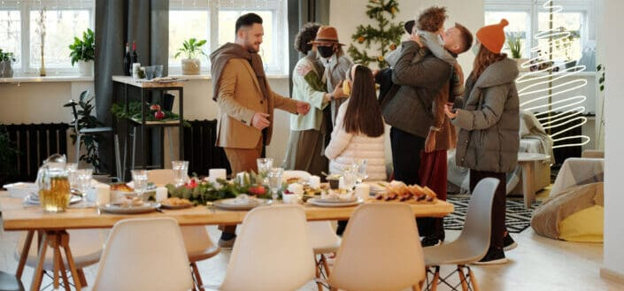 a group of people greeting each other by a dining table