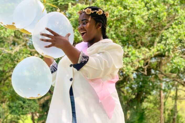 woman holding white balloons looking fascinated