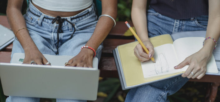 2 women sitting beside each other, one holding a laptop, the other holding a notebook