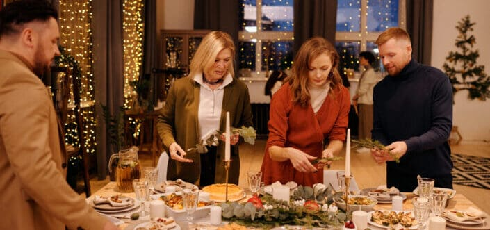 four people preparing their christmas table decoration