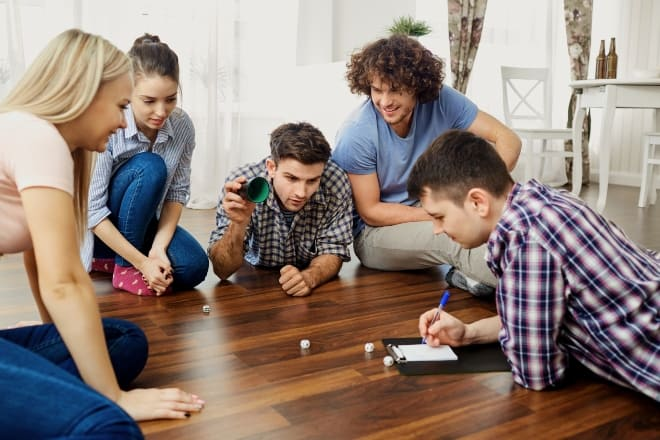 group of people sitting on a wooden floor playing a game of dice - minute to win it games