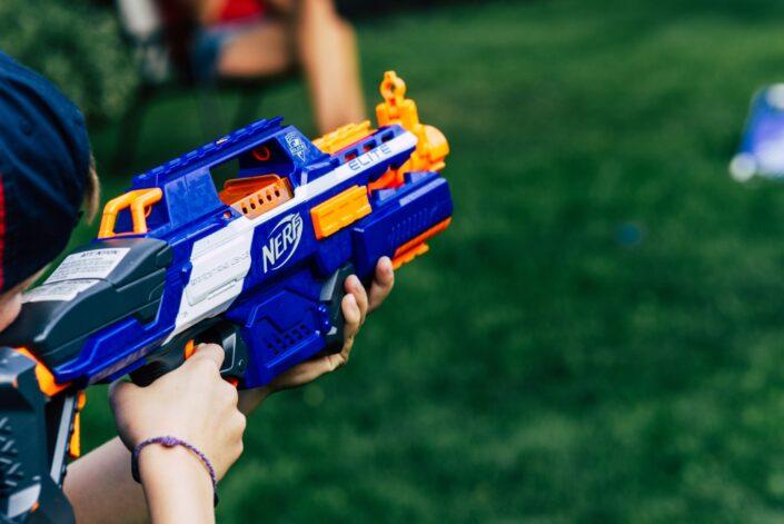 a boy aiming a nerf gun