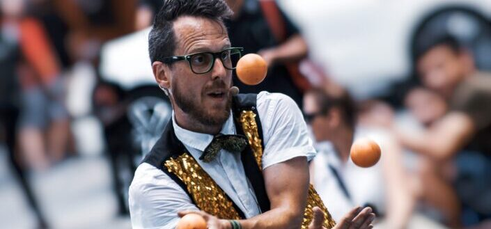 a man wearing wearing eyeglasses juggling 3 balls at a time