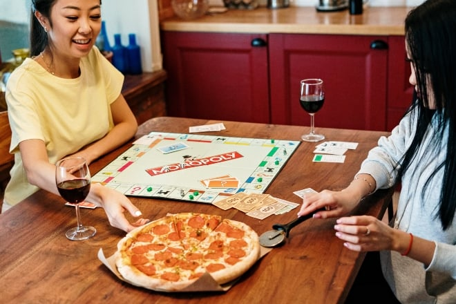 girls eating pizza while playing monopoly - party board games