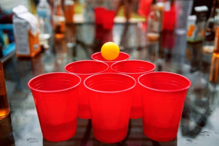 six red cups arranged in a triangle pattern with an orange pingpong ball about to fall into one