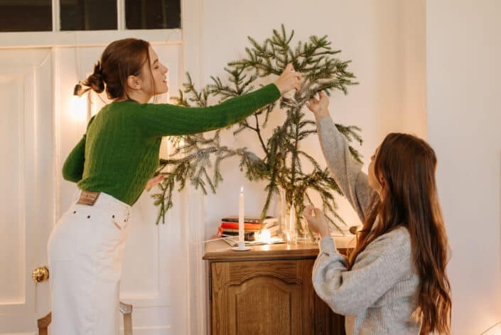 two women setting up a tree inside the house