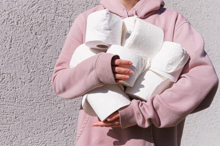 guy holding 8 rolls of tissue paper