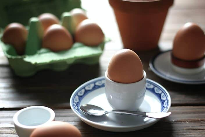 hardboiled egg on an egg plate with a spoon on the side