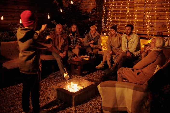 group of adults playing charades around a firepit