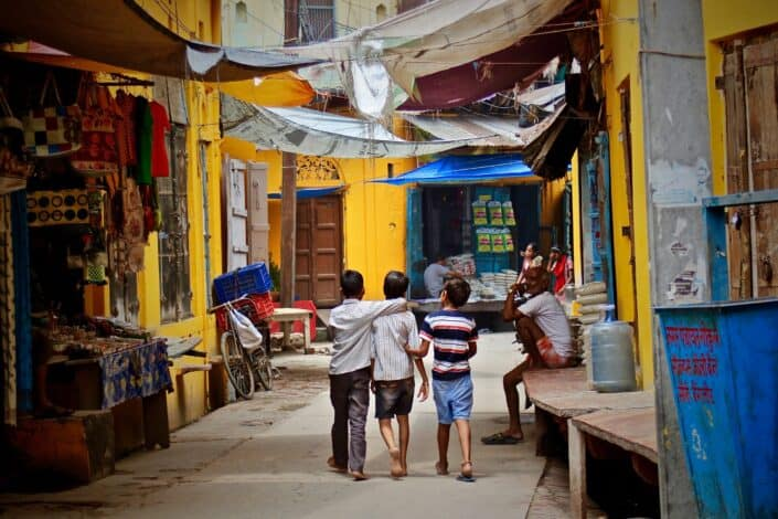 three little boys walking down a colorful alley