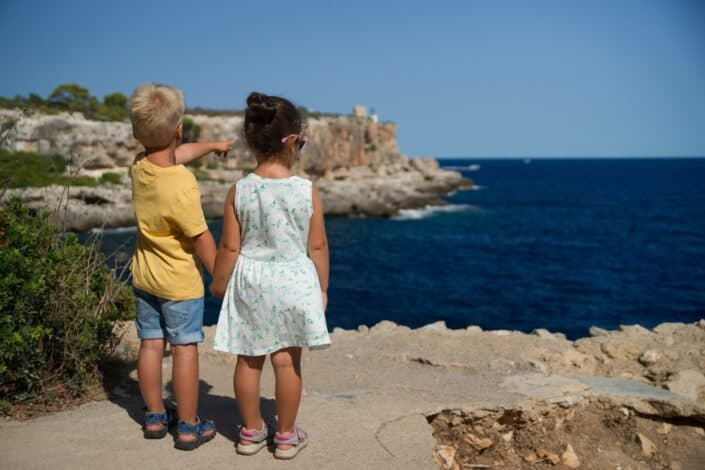 boy and girl holding hands over a cliff