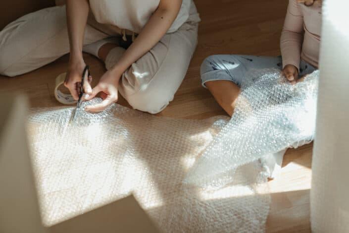 girls cutting bubble wrap on floor