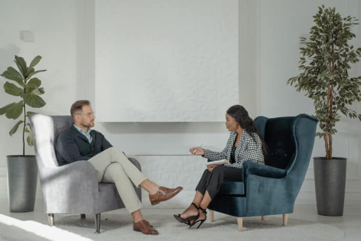 Two people talking while sitting on chairs