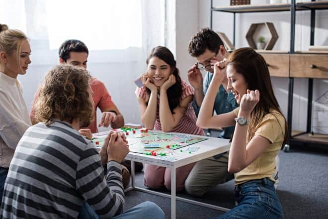 A group of people happily playing - Funny Board Games
