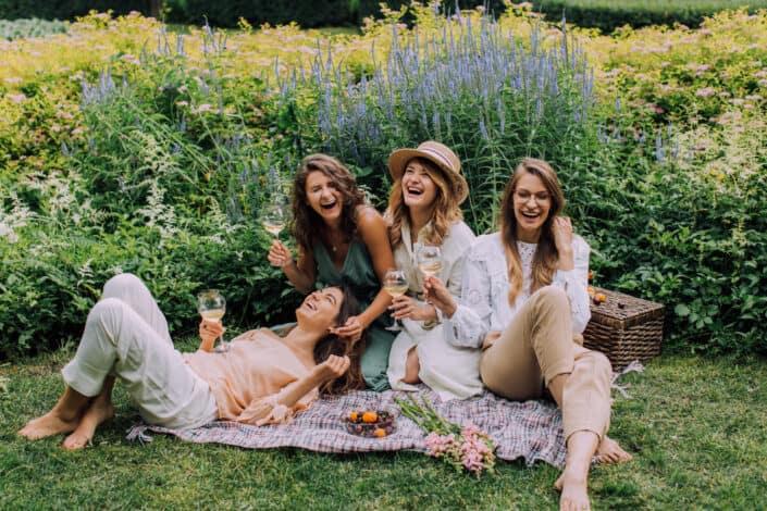four ladies having a fun picnic outside
