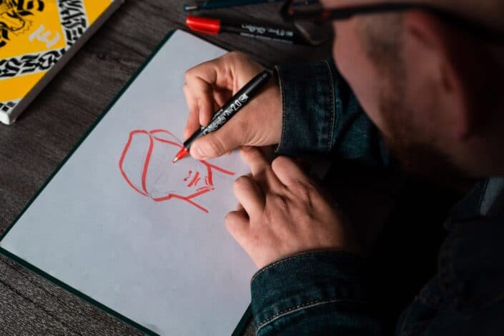 a man sketching on a white paper