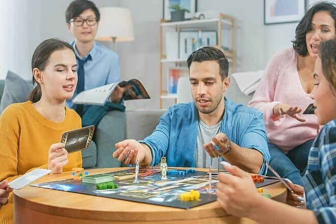 friends playing a board game - board games for adults