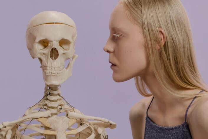 woman looking seriously at human skeleton
