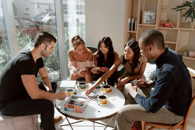 group of people playing board games - dinner party games for adults