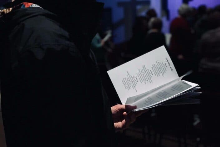 Printed song lyrics being held by person
