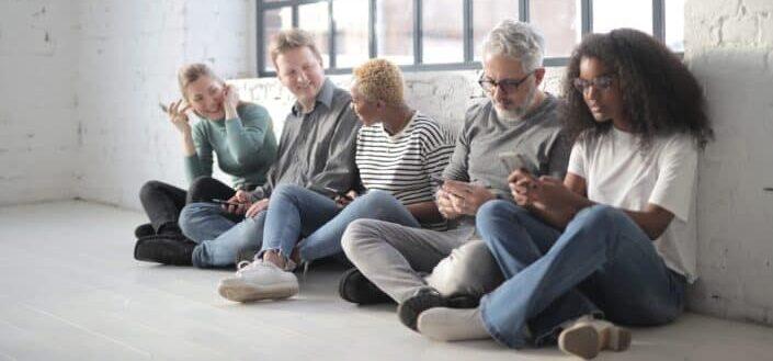 happy multiracial colleagues using smartphones