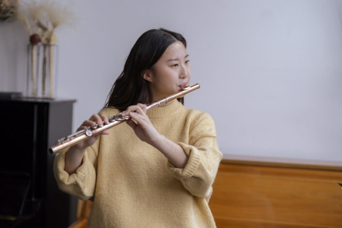 Girl in faded yellow sweatshirt playing a flute.