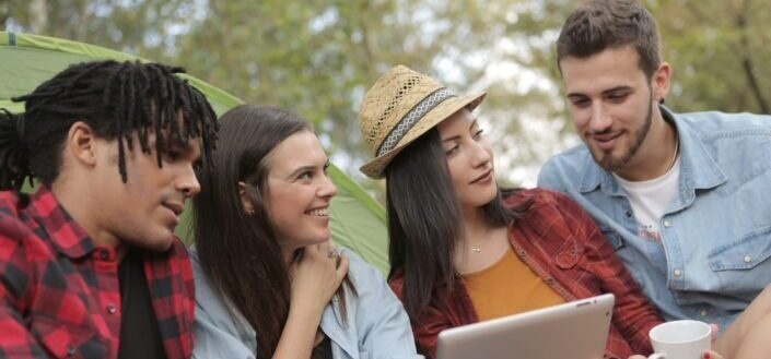 happy multiethnic people using tablet on camping