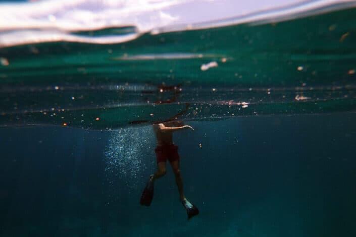 man in water wearing black shorts