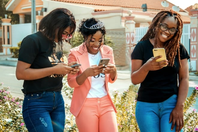 cheerful girlfriends in stylish clothes chatting on smartphones - games to play over text