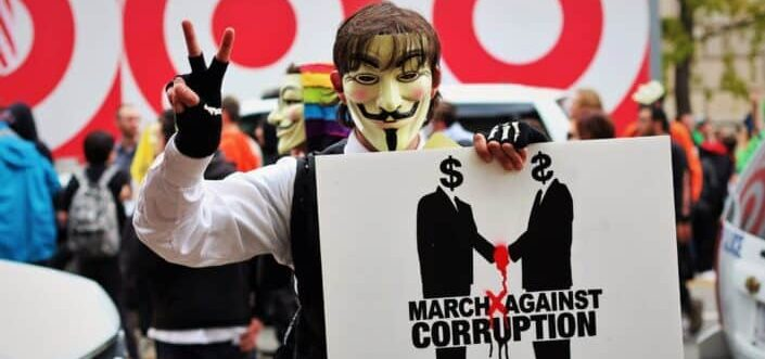 masked person holding a political banner